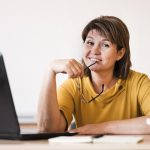 female-teacher-with-laptop-sitting-at-desk