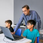 Teacher in glasses standing behind pupil and checking task on laptop. Little classmates and students sitting at table in school and using computers for study. Knowledge and digital education concept